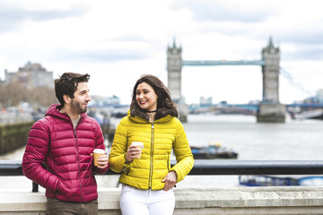 UK, London, couple with coffee to go standing on bridge over the Thames