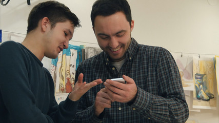 Two positive art students laughing at something on the phone