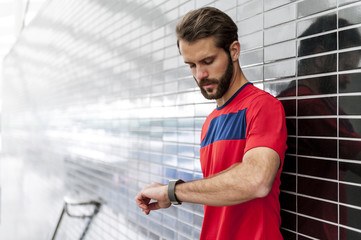 Man having a break from running checking the time on a smartwatch