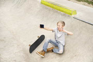Germany, North-Rhine-Westphalia, Cologne, boy taking selfies with smartphone in skatepark