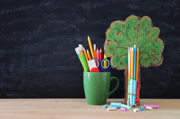 Back to school concept. tree of knowledge and pencils in front of classroom blackboard.