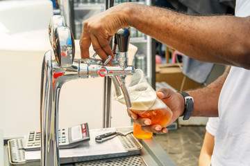 barman's hand holds a large glass in which fresh amber beer is poured with foam. Street trading