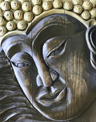Buddha face executed with antique style, wood carving. Handmade, bas-relief wooden