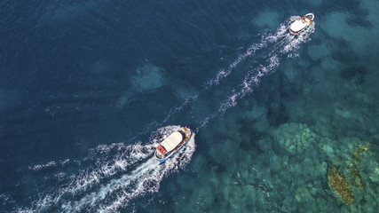 Aerial view of two white motorboats running on the azure waters of the Tyrrhenian Sea. On his trip near the coast the boat leaves a white trail in the waves of the sea.