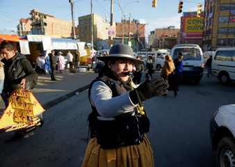 Elizabeth Acho, a municipal guard,directs the vehicular traffic in El Alto outskirts in La Paz