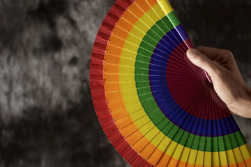 man with a rainbow-patterned hand fan.