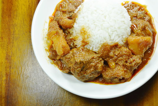 pork curry and potato with rice on plate