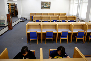 Students study in a library where a picture depicting former North Korean leader Kim Il Sung is displayed on the wall at Korea University in Kodaira