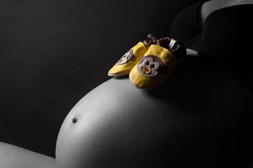 Babybauch mit gelben Schuhen