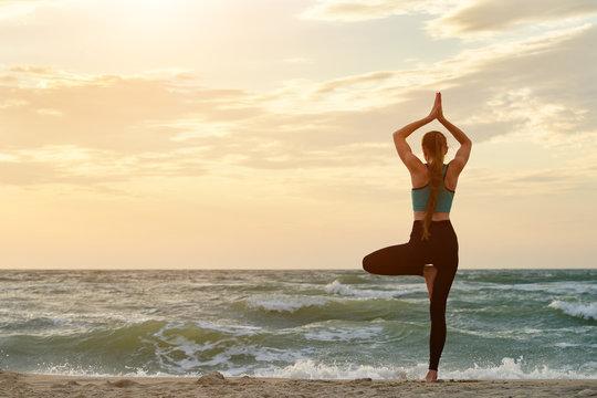 Girl on sea beach practicing yoga. Back view. Beautiful sunlight