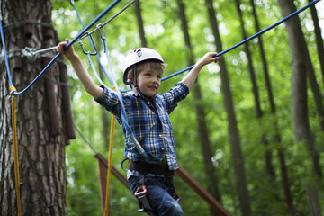 boy enjoys climbing in the ropes course adventure. smiling child engaged climbing high wire park.