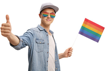 Teenager with a rainbow flag and glasses making a thumb up gesture