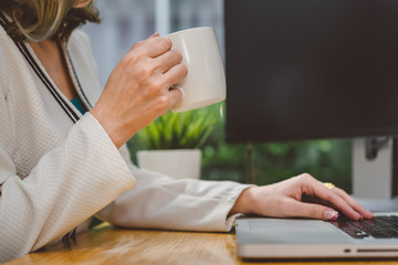 Businesswoman working with laptop computer and drinking coffee break from cup at workplace table office in the morning