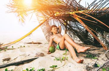 Boy sleeps in selfmade hut on tropical beach