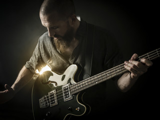 Bearded man playing bass guitar