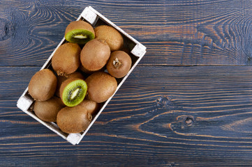 Fresh ripe kiwi fruit in a wooden box on the table. Tropical Fruit. Healthy food. Top view.