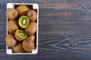 Fresh ripe kiwi fruit in a wooden box on the table. Tropical Fruit. Healthy food.