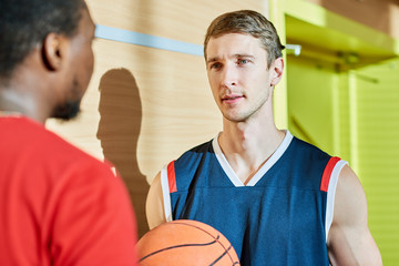 Two basketball players standing in gym and having nice conversation before match.