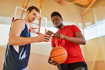 Two basketball players standing on court in gym and browsing smartphone together.