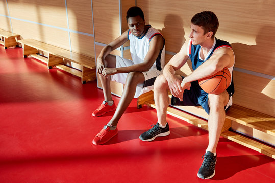 Two basketball players with ball resting on bench during training in gym.