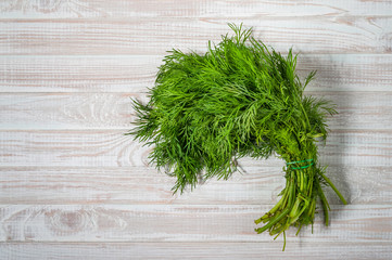 green dill on white wooden background