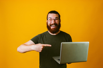 Cheerful bearded hipster man poiting at laptop over yellow background