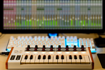 midi keyboard, audio signal level on screen. music production, home studio concept