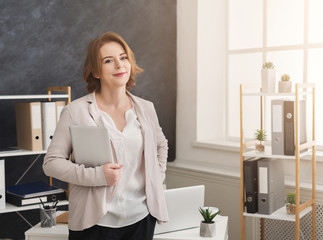 Confident businesswoman holding digital tablet at workplace