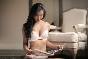 Beautiful woman in white lingerie reading a magazine