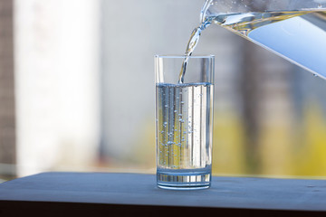 A glass beaker is filled with clean water in the open air. Summer sunny day. Theme of a healthy lifestyle