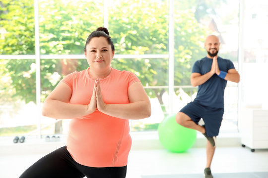 Overweight man and woman practicing yoga in gym