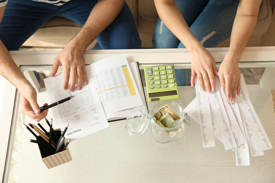 Couple with pay bills, calculator and money counting expenses indoors. Money savings concept