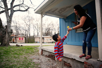 Isai Rodriguez, 5, picks a flower and gives it to his mother Morena Vasquez as they wait for a church van to pick them up and take them to church in Rome, Georgia