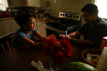 Arturo Flores and his daughter Alma Quiterio, 17, spend time on their cellphones at home in Concord, North Carolina
