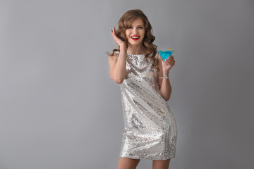 Beautiful young woman with cocktail on grey background