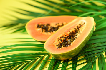 Exotic papaya fruit over tropical green palm leaves on yellow background. Copy space. Pop art design, creative summer concept. Raw vegan food.