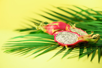 Pitahaya or dragon fruit over tropical green palm leaves on yellow background. Copy space. Pop art design, creative summer concept.