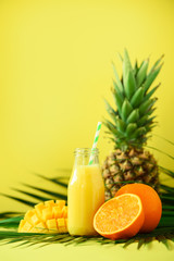 Delicious juicy smoothie with orange fruit, mango, pineapple on yellow background. Copy space. Pop art design, creative summer concept. Fresh juice in glass jar over green palm leaves.