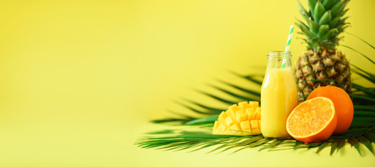 Delicious juicy smoothie with orange fruit, mango, pineapple on yellow background. Copy space. Pop art design, creative summer concept. Fresh juice in glass jar over green palm leaves. Banner