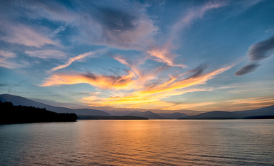 Dramatic Sunset with Blue Sky at the Ashokan Reservoir in Ulster County in New York. Golden light reflects on the Mountains and calm reservoir surface.
