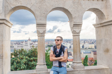 Young man in sunglasses are photographed in the background of Budapest