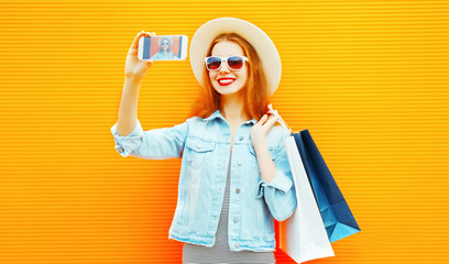 Stylish happy woman takes a picture self portrait on a smartphone on a orange background