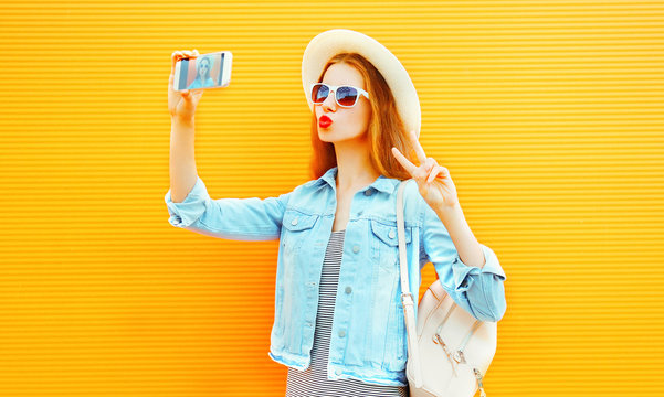 Pretty girl takes a picture self portrait on a smartphone on orange background