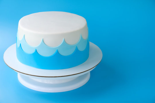 Сake for the child's birthday, decorated with sea waves on a blue background. Picture for a menu or a confectionery catalog.