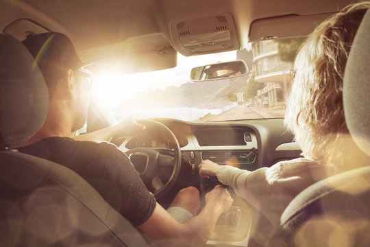 Junges Pärchen im Auto bei Sonnenuntergang
