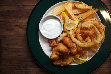 Fish and chips fried fish and potatoes on wood background vintage style