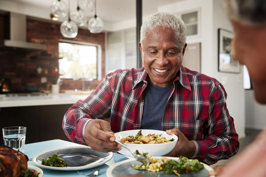 Senior Couple Enjoying Meal Around Table At Home