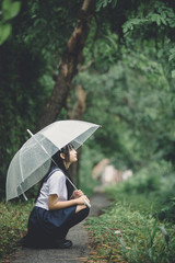 Portrait of Asian school girl sitting with umbrella at nature walkway on raining