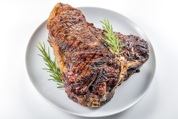 White round plate with Whole grilled T-bone steak and rosemary
