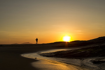 Athlete running on the beach of Macaé Rio de Janeiro Brazil at sunrise